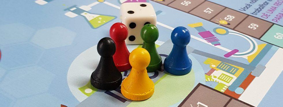 Foto artística dos peões e dado do jogo de empreendedorismo Mente Empreendedora