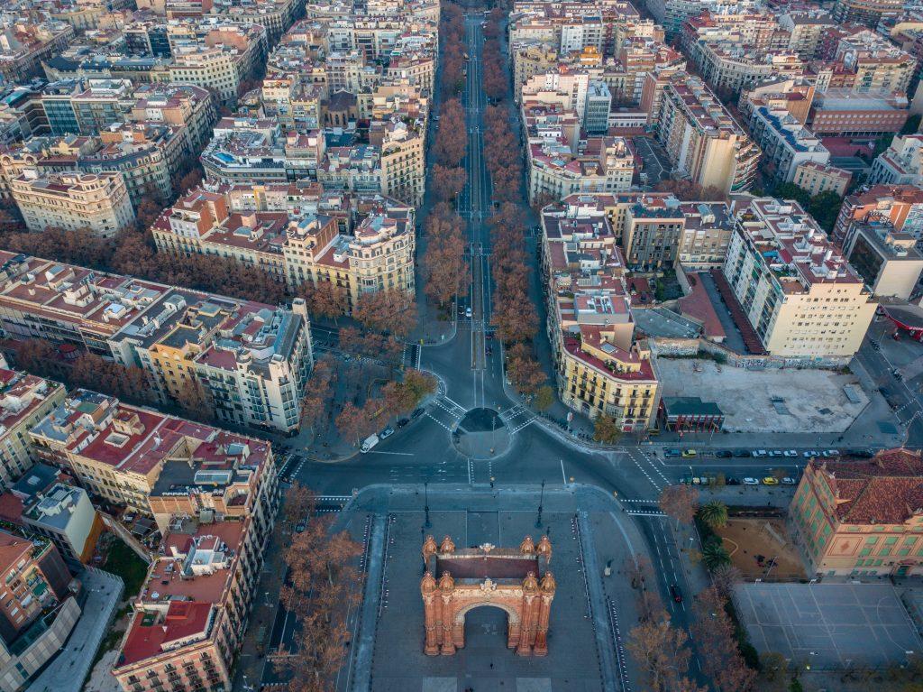 Cidade de Barcelona, vista aérea das ruas. Aparecem ruas, prédios, carros, áreas verdes.